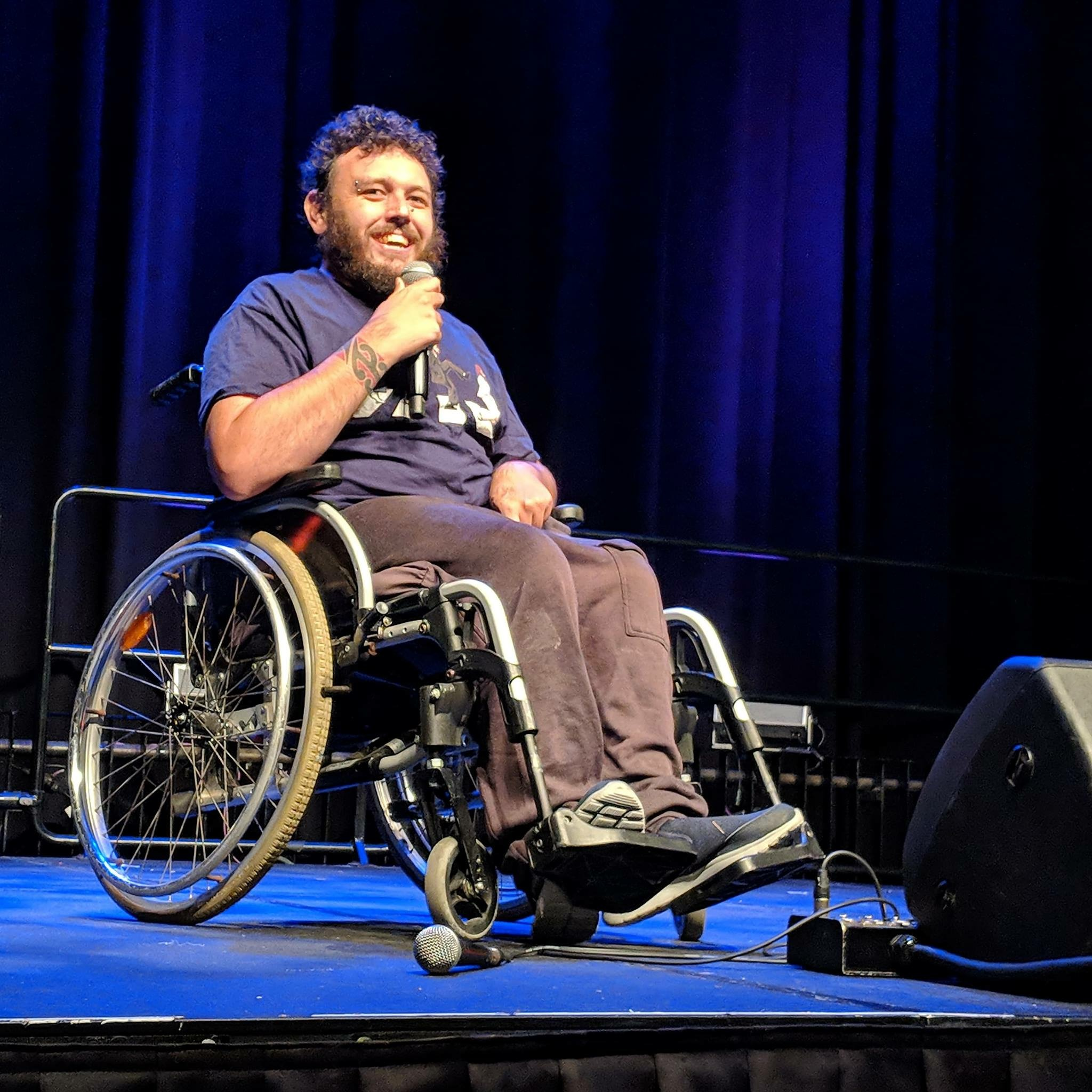 Richie pictured onstage in his wheelchair, holding a microphone and smiling