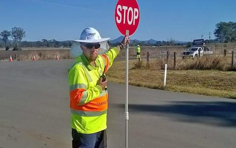 Beau standing beside a road wearing hi vis shirt and safety hat. He is holding a stop sign out beside him